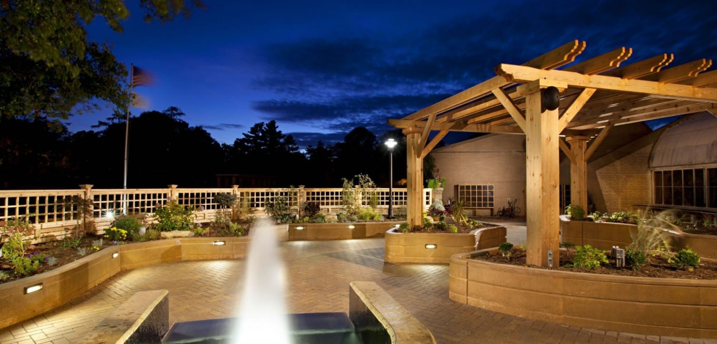 Garden patio at night with fountain and wooden canopy