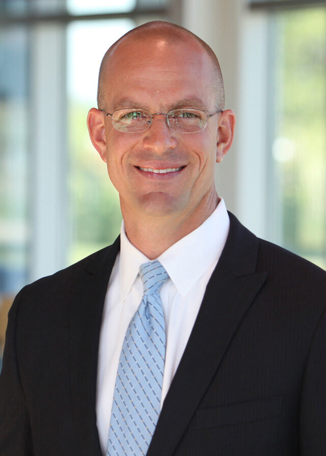 Professional white bald man in a suit wearing glasses.