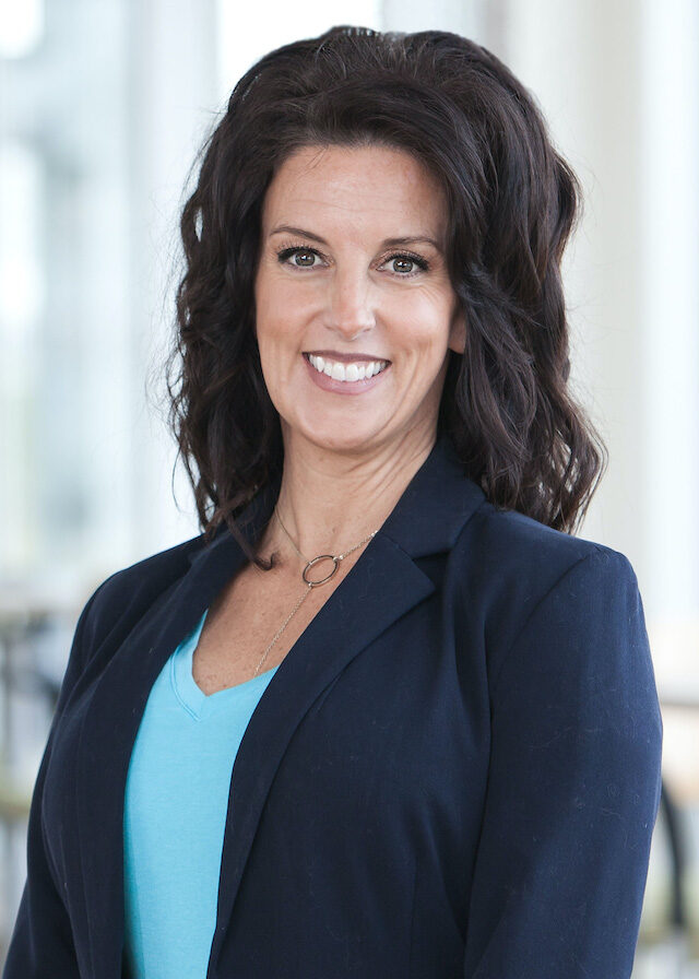 Professional white woman with dark hair and suit jacket.