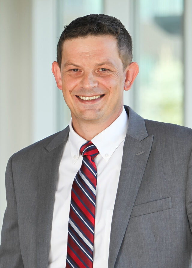 Dark-haired white male professional wearing a gray suit.