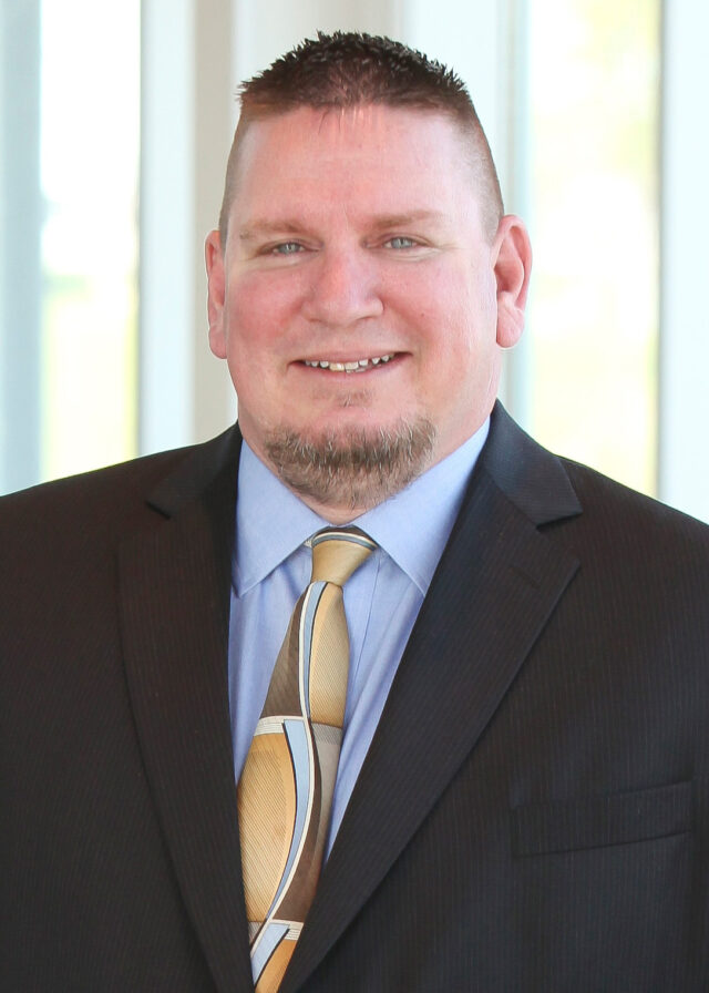Heavyset white male professional with short-cropped hair and chin beard wearing a suit.