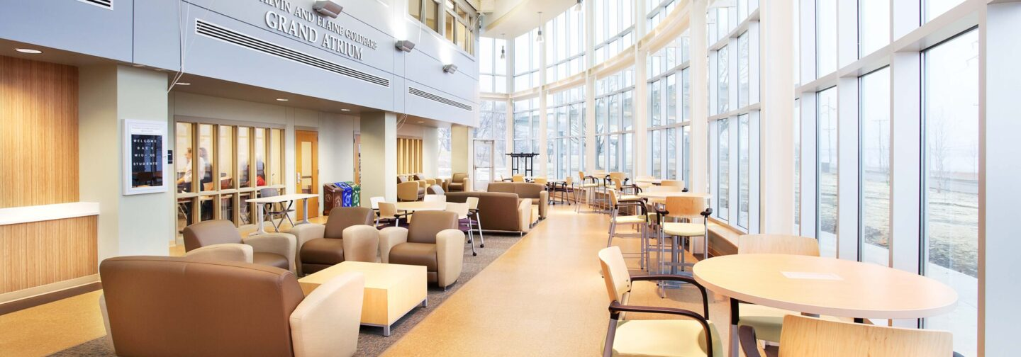 A modern campus interior with a curved glass wall on the right and an atrium entrance on the left.