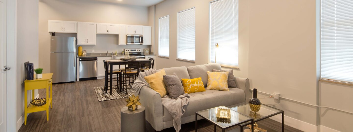This image displays a living room and kitchen at Hershey Lofts in Muscatine, Iowa