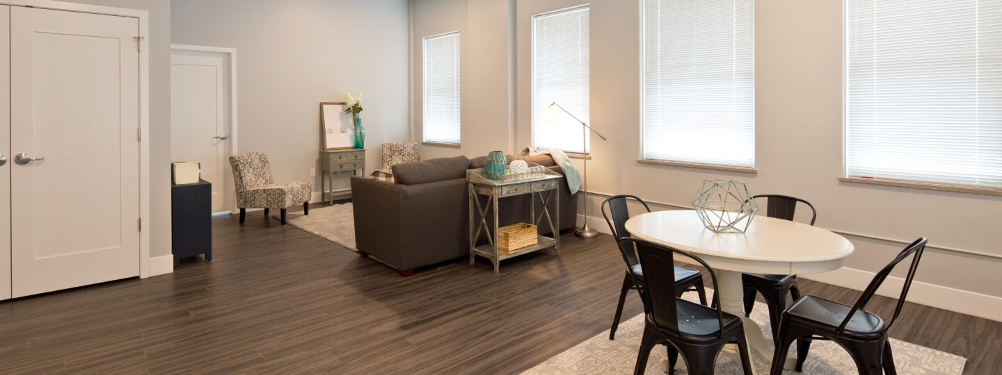 This image displays an opening living room and dining room at Hershey Lofts in Muscatine, Iowa